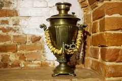 Ancient copper Russian samovar with bagels on the background of a red brick oven. Background, retro, vintage stock photo