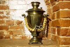 Ancient copper samovar stands in the form of decorations with lamb products on the background of the wall of the Russian red brick stock photography