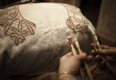 Ancient craft. The Needlewoman is Weaving graceful Lace Royalty Free Stock Photos