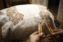 Ancient craft. The Needlewoman is Weaving graceful Lace Stock Photo