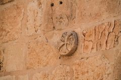 Ancient cross carving on brick wall in Jerusalem royalty free stock photography