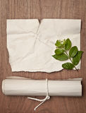Ancient crumpled paper scroll on wood table with green leaf for background Stock Photos