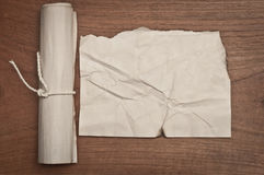 Ancient crumpled paper scroll on wood table may use for background. Ancient crumpled paper scroll on wood table Royalty Free Stock Image
