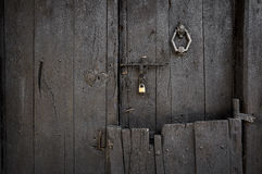 Ancient dark brown wooden door with a door knocker a padlock and a bolt Stock Image