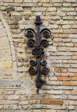 Ancient decorative wrought iron on brick wall.  Stock Photo