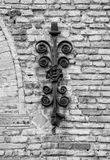 Ancient decorative wrought iron on brick wall. Black and white Royalty Free Stock Images