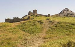 An ancient defensive fortress on a hill overgrown with green grass. Royalty Free Stock Image