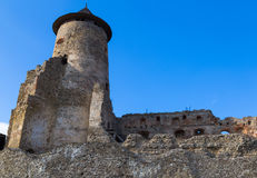 Ancient defensive tower and partially destroyed fortress wall. Ancient defensive tower and partially destroyed fortress wall against the bright blue sky. Castle royalty free stock photography