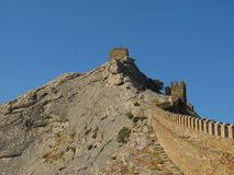 Defensive Genoa wall on the mountain against the blue sky. Ancient defensive wall of Genoa fortress, Crimea, Sudack Royalty Free Stock Photo