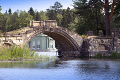 The ancient destroyed bridge in park and pavilion of Venus (1793) is visible under a bridge arch. Gatchina, St. Petersburg, Russia.  Stock Image