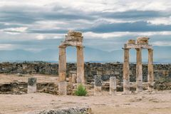 The ancient destroyed city of Hierapolis near Pamukkale, Denizli, Turkey in the summer. On a background the sky in overcast. Horiz. The ancient destroyed city of Stock Images