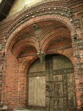 Ancient door in the brick wall with tiles Royalty Free Stock Photography