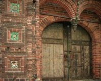 Ancient door in the brick wall with tiles Stock Photos