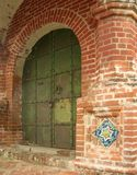 Ancient door in the brick wall with tiles Stock Image