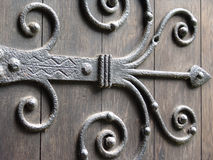Ancient door hinge. Ancinet wrought iron ornate door hinge on old door stock images