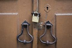 Ancient door knockers, lock and a padlock of an ancient brown wooden door Royalty Free Stock Photo