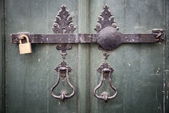 Ancient door knockers, a metallic bar and a padlock on an ancient green wooden door Stock Photos