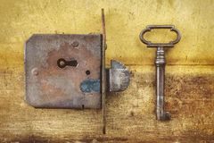 Ancient door lock with key on a metal background Stock Photography