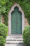 Ancient door in a luxurious vegetation vertical Royalty Free Stock Photo