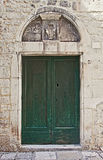 Ancient door painted green with architrave Stock Photos