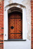 Ancient door on a red brick wall Royalty Free Stock Photography