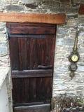 Ancient door and vintage wall clock. Ancient door, wood, old house and vintage wall clock royalty free stock photo