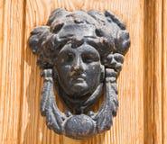 Ancient doorknocker. Ancient doorknocker shaped woman face Stock Photography