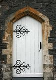 Ancient Doorway. Old stone arched doorway with white wooden doors and black wrought iron accessories Royalty Free Stock Images
