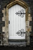 Ancient Doorway. Old stone arched doorway with white wooden doors and black wrought iron accessories Stock Photos