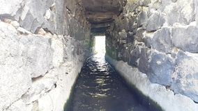Ancient drainage tunnel of stone for drinking water, water current, Geghovit, Armenia