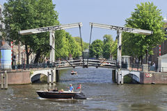 Ancient drawbridge with a boat. AMSTERDAM-AUG. 19, 2012. Drawbridge on Aug. 19, 2012 in Amsterdam. It is known as Venice of the North. The city has 1,200 bridges Stock Photo