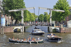 Ancient drawbridge with vessels in Amsterdam. AMSTERDAM-AUG. 19. Boats in canal with drawbridge. It is known as Venice of the North, it has 1,200 bridges and 165 Stock Images