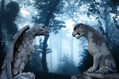 Ancient eagle and lion statues in misty forest. Ancient eagle statue and lion statues in mysterious landscape of foggy forest royalty free stock photo