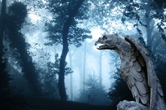 Ancient eagle statue in misty forest Stock Image