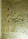 Ancient Egyptian carving, Seti and Horus. Ancient Egyptian bas relief wall carving showing the Pharaoh Seti I making an offering to the falcon headed god Horus Royalty Free Stock Images