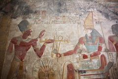 Ancient Egyptian engravings. Seti wearing a blue crown burning incense over an offering Stock Image