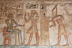 Ancient Egyptian engravings. Seti wearing a blue crown burning incense over an offering Royalty Free Stock Photo
