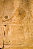 Ancient Egyptian God Khnum. Carved stone frieze of the ancient egyptian god Khnum in human form with a crown of ram's horns on his head. Interior of the Temple Royalty Free Stock Photography