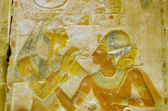 Ancient Egyptian goddess Hathor with Pharaoh Seti. An ancient egyptian hieroglyphic carving showing the goddess Hathor, with her cow horn crown, placing the Royalty Free Stock Images