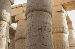 Ancient egyptian hieroglyphic carvings on columns in temple. Columns with hieroglyphiarvings in hypostyle hall at anciant egyptian Karnak Temple in Luxor stock image