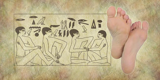 Ancient Egyptian Hieroglyphics of Reflexology. Pair of female feet on right with Egyptian hieroglyphic panel of foot massage scene on stone effect background Royalty Free Stock Image