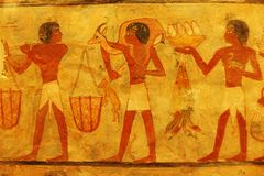 Ancient Egyptian painting in Louvre. A photograph showing the beautiful drawing art of ancient Egypt, showing people workers bringing produce and hunted animals royalty free stock image