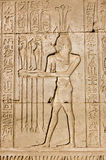 Ancient Egyptian priest for Hapi god. Ancient Egyptian hieroglyphic carving of a priest making an offering to Hapi, the god of the Nile. Shown by the lotus on stock image