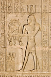 Ancient Egyptian priest for Ra and Ka Gods. Ancient Egyptian bas relief sculpture of a priest making an offering to the gods Ra and Ka.  Outer wall of Dendera Stock Image