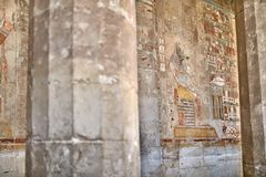 Ancient egyptian temple wall covered with hieroglyphics and images in Luxor. Old egyptian wall with hieroglyphs and colorful images of the god Anubis and humans royalty free stock photo