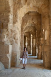 In ancient El Jem. The Roman Colosseum in El Djem is one of the largest Colosseums. Young woman  walks along one of galleries that  rounds up the audience space Royalty Free Stock Photos