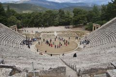 The ancient Epidauros theatre, built in the 4th century BC. Peloponnese, Greece. A great tourist attraction. Visitors on the stairs and on stage. South-east stock photos
