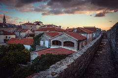 Ancient European city skyline with orange tile roofs and dramatic sky during sunset in antique architecture in old European town Stock Photography