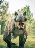 Ancient extinct dinosaur tyrannosaurus. On a background of plants stock photos