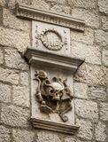 Ancient family coat of arms in the form of a skull with snakes on the wall of an old building in the city of Kotor, Montenegro.  royalty free stock photos